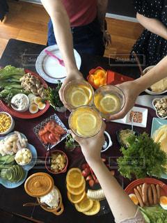食べ物の皿を持ってテーブルに座っている女性の写真・画像素材[2816026]