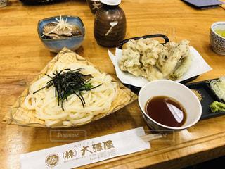 木製テーブルの上に座って食品のプレートの写真・画像素材[1933954]