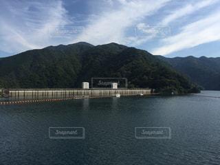 背景の山が付いている水の体の上の橋の写真・画像素材[780836]
