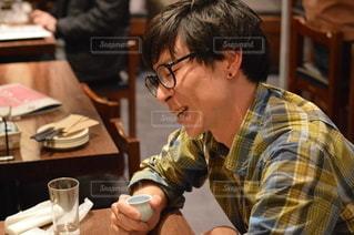 食べ物を食べるテーブルに座っている男の写真・画像素材[3005380]