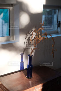 木製のテーブルの上に座っている花瓶の写真・画像素材[3218266]