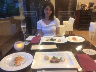 食品のプレートをテーブルに座っている女性の写真・画像素材[1926338]