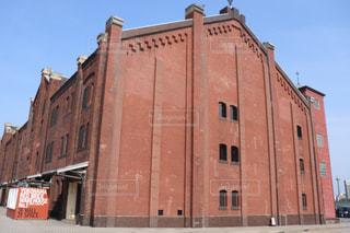建物の側面に時計を持つ大きな赤レンガの塔の写真・画像素材[2340676]