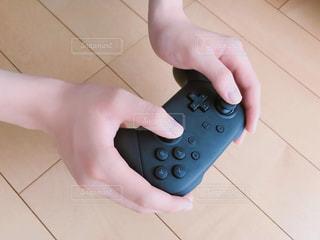 ゲームのコントローラを握る手の写真・画像素材[2305439]