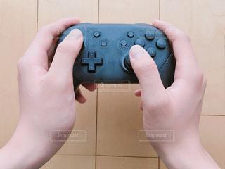 ゲームのコントローラを握る手の写真・画像素材[2305440]