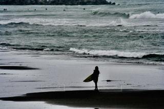 サーフィンを終えて浜辺を歩く女性の写真・画像素材[2290123]