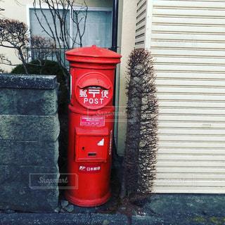建物の側に座っている赤い消火栓の写真・画像素材[1940240]