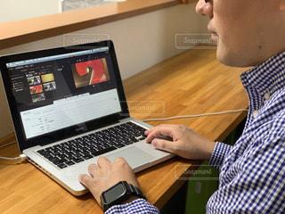 木製のテーブルの上に座っているラップトップコンピュータを使用している男の写真・画像素材[2320227]