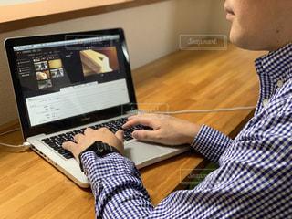 木製のテーブルの上に座っているラップトップコンピュータを使用している男の写真・画像素材[2320229]