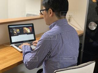ラップトップコンピュータを使ってテーブルに座っている男の写真・画像素材[2320230]