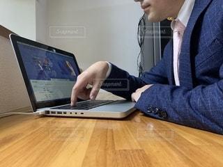 ノートパソコンを使ってテーブルに座っている人の写真・画像素材[2320240]