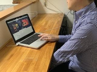 テーブルの上に座っているラップトップコンピュータを使っている男の写真・画像素材[2320247]