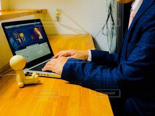 ノートパソコンを使ってテーブルに座っている男の写真・画像素材[2320257]
