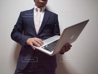 ノートパソコンの前に立っている人の写真・画像素材[2322630]