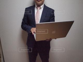 ラップトップの前に立つスーツとネクタイを着た男の写真・画像素材[2322646]