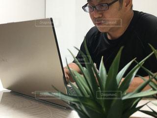 ノートパソコンを使ってテーブルに座っている男の写真・画像素材[2367310]