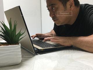 ラップトップコンピュータを使ってテーブルに座っている男の写真・画像素材[2367311]