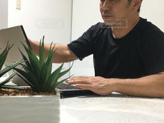 花瓶のあるテーブルに座っている人の写真・画像素材[2367312]