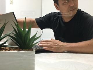 ノートパソコンを使ってテーブルに座っている人の写真・画像素材[2367313]