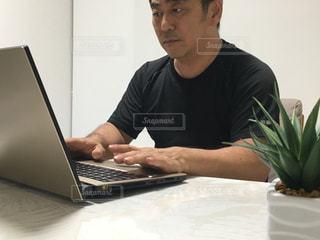 ラップトップコンピュータを使ってテーブルに座っている人の写真・画像素材[2367315]