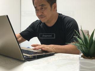ラップトップコンピュータを使ってテーブルに座っている男の写真・画像素材[2367316]