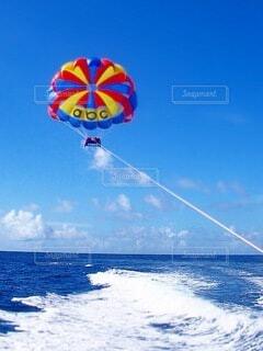 大きな水域で凧を飛ばす男の写真・画像素材[4190083]