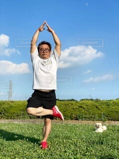 芝生で覆われた野原の上で空を飛んでいる人の写真・画像素材[4657913]