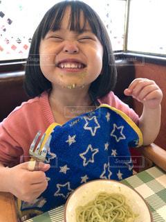 食べ物の皿のテーブルに座っている小さな女の子の写真・画像素材[2212916]