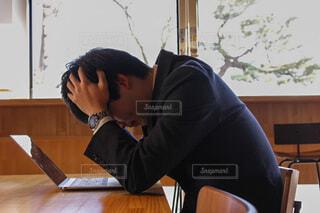 机で頭を抱えて1人で落ち込む男性の写真・画像素材[3971026]