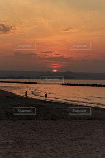 水の体の横にビーチに沈む夕日の写真・画像素材[764056]