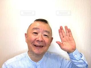 手を上げて微笑む男性の写真・画像素材[3451362]