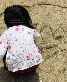 地面に絵を描く少女の後ろ姿の写真・画像素材[2098244]