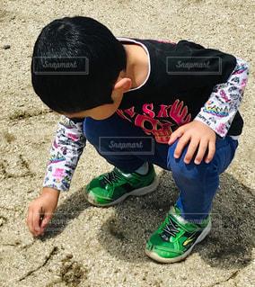 地面に座っている小さな男の子の写真・画像素材[2103539]