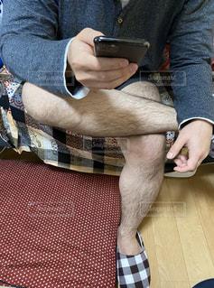 携帯電話を触り寛ぐ男性の写真・画像素材[3124928]