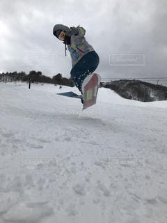 雪の空気中のジャンプ男覆われた斜面の写真・画像素材[1012051]