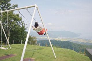 山を背景にブランコをする人の写真・画像素材[2419131]