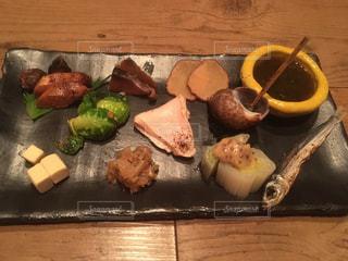 木製のテーブルの上に座っている食べ物の束の写真・画像素材[2868501]