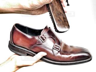 青と黒の靴を履いた足革靴を磨いている手の写真・画像素材[2288772]