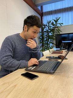 テーブルの上に座っているラップトップコンピュータを使う少年の写真・画像素材[2879517]