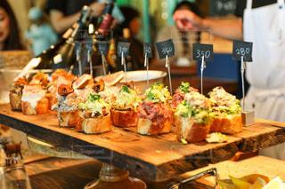 食物と一緒にテーブルに座っている人々 のグループの写真・画像素材[1317395]