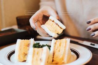 喫茶店でサンドイッチを手に取る女子の写真・画像素材[1671303]