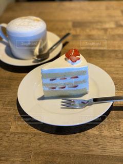 コーヒーを飲みながら皿にケーキを置くの写真・画像素材[2935827]