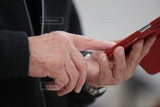 携帯電話を操っている年配の男性の手の写真・画像素材[2129500]