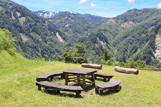 山中の道沿いにある木製のテーブルとベンチの写真・画像素材[2146558]