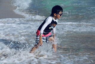 水上のサーフボードの上で波に乗っている男の写真・画像素材[2117590]