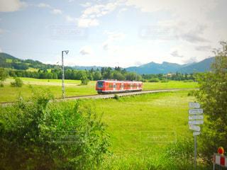 緑豊かな緑のフィールドを介して走行する列車の写真・画像素材[2078237]