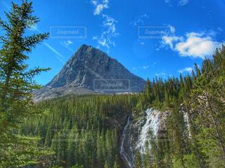 降り注ぐ太陽の中の山と滝の写真・画像素材[2111369]