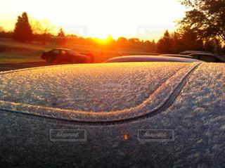 サンライズをバックに車に霜が降りているところを写しました。の写真・画像素材[2130191]