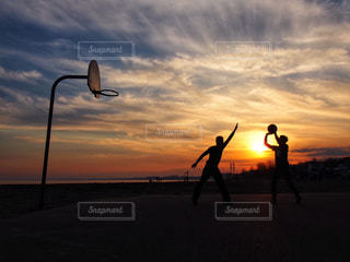 沈んでいく太陽とバスケをしている人たちの写真・画像素材[2165086]