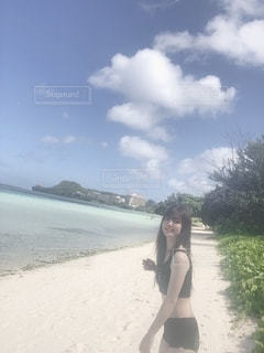 カメラに向かってポーズをとっているビーチに立っている女性の写真・画像素材[2771267]